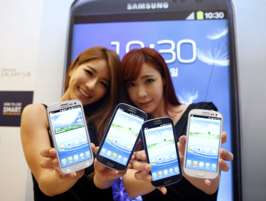 Models hold new Galaxy S III devices as they pose for photographers during an event to launch the smartphone in the local market at the headquarters of Samsung Electronics in Seoul June 25, 2012. Samsung Electronics expects sales of its new Galaxy S III, launched at the end of last month as a main rival to Apple's iPhone, to top 10 million during July, making it the South Korean group's fastest selling smartphone. REUTERS/Lee Jae-Won (SOUTH KOREA - Tags: BUSINESS TELECOMS SCIENCE TECHNOLOGY) - RTR344E2